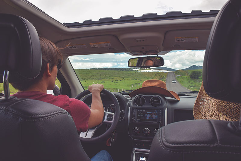 list of road trip gifts. man driving a car with a cowboy hat on the dashboard and the skylight open