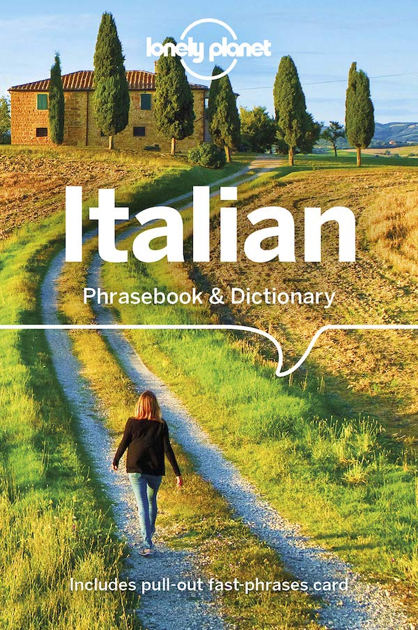 italian phrasebook. cover has a blonde woman in a black shirt and jeans walking down a gravel path toward a stone villa