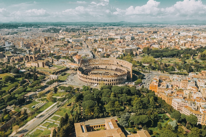 Italy from above with the colosseum in the center of the photo and the city sprawling out.
